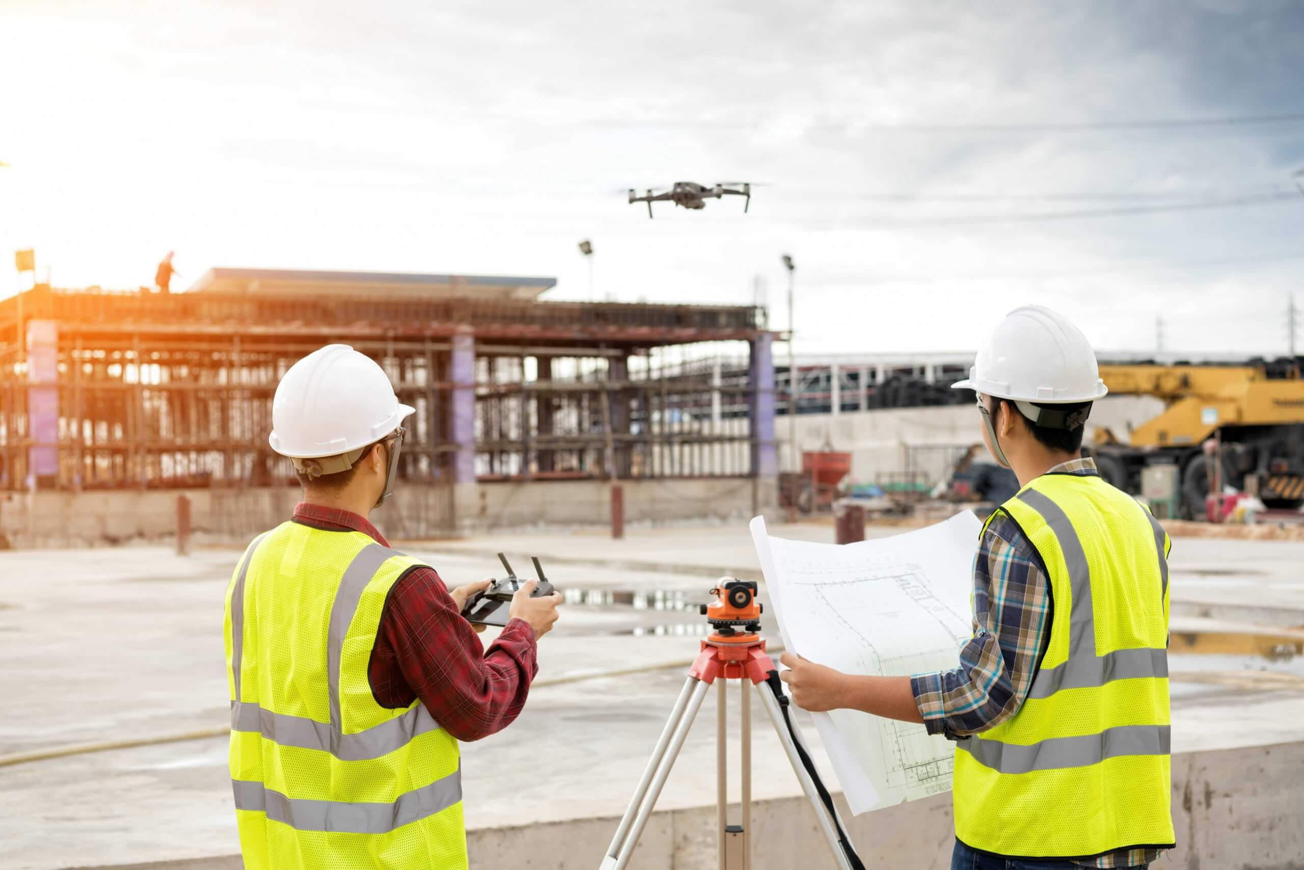 two construction workers using drone to survey site